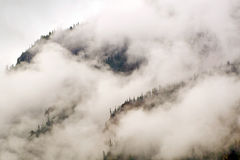 Mist Clouds and Fog Shroud this Colorado Rocky Mountain Bluff Face Stock Photography