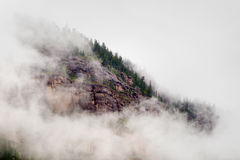 Mist Clouds and Fog Shroud this Colorado Rocky Mountain Bluff Face Stock Images