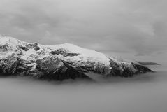 Between mist and clouds. Monochrome mountain landscape in foggy weather in winter Royalty Free Stock Image