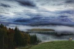 Mist covered valley and mountains Stock Photo