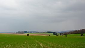 Mist and dark clouds over Ardennes farm landscape,. Landscape with fog and dark clouds over the green fields and hills with forests of the Ardennes  in Liege Royalty Free Stock Photography