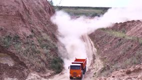 Mist of dust on the country road after big truck passing. Scene. Heavy, red excavator rides on a dusty dirt road at a. Mist of dust on the country road after big stock video footage