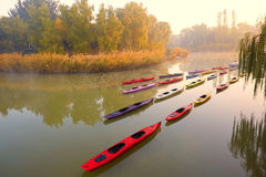 Mist morning Beijing Olympic Forest Park. Foggy and sunny morning, lakescape and Kayak boats in sunrise Royalty Free Stock Images