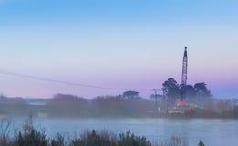 Mist Morning Bridge Crane. Early morning mist around a bridge building crane on the Manawatu river Royalty Free Stock Photos