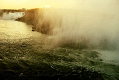 Mist of Niagara Falls. This image is of Niagara falls in the early morning. The shot contains Powerful elements of nature. The morning sun rising, Rapids, water Royalty Free Stock Images