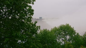 Mist from Niagara Falls. Mist rising from the Niagara Falls covers the scenery.  Green trees in the forefront stock footage