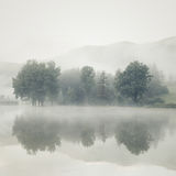 Mist On A Lake At Dawn With Trees And Mountains Reflected In The Royalty Free Stock Image