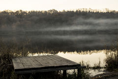 Mist over het meer riet en houten pier Stock Fotografie