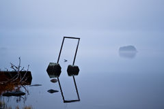 Mist over a lake. Vigorous mist over a lake. An island is visible through the fog Stock Photography