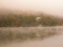Mist over the lake with colorful trees and house. Royalty Free Stock Images