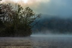 Mist over lake in sunny colorful morning stock photos