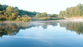 Mist over the river. Autumn beautiful landscape of forest is reflected in the water on the riverbank. Mist over the river. Autumn beautiful landscape of forest stock footage