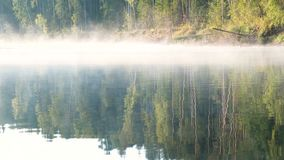 Mist over the river. Autumn forest is reflected in the water on the riverbank. Mist over the river. Autumn forest is reflected in the water stock video footage