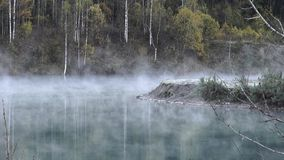 The mist over the water. The mist over the water above the lake. Autumn. September. Old flooded quarry Sosnovka near the city of Mezhdurechensk. On the coast stock video
