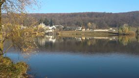 Mist rises from the water. Autumn landscape of a forest in beautiful fall colors reflected in the waters of a lake.Monastery on the shore of the lake stock footage