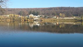 Mist rises from the water. Autumn landscape of a forest in beautiful fall colors reflected in the waters of a lake.Monastery on the shore of the lake stock video