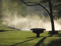 Mist Rising off a Country Pond. Morning mist on a country pond with a tree and urn in silhouette Royalty Free Stock Photos
