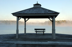 Mist rising off lake. A beautiful gazebo in cottage country overlooking a lake with mist rising in early morning royalty free stock images