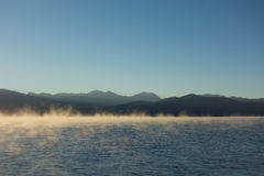 Mist rising off a mountain lake in the summertime Stock Photos