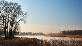 Mist rising from the river in the morning. The smoke from the chimney on blue sky Royalty Free Stock Photos