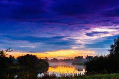 Mist Rising From The River During Sunset. The autumn coldness makes the mist rise from the warm water of the river. The sunset creates quite dramatic colors on stock images