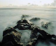 Mist among rocks at coast Stock Photography