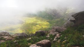 Mist rolling over sun lit valley under Andringitra massif, as seen during trek to pic Boby aka Imarivolanitra, highest accesible