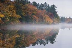 Mist svävar längs en sjö som reflekterar en New England höst royaltyfria bilder