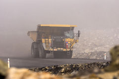 Through the mist. A 130 ton tiptruck emerges from the mist at an open cast coal mine, Westland, New Zealand Royalty Free Stock Image