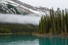 A mist and turquoise water of the Maligne lake, Alberta, Canada. Peaceful staggering view of turquoise water at the Maligne lake, green island and sharp snowy Royalty Free Stock Image