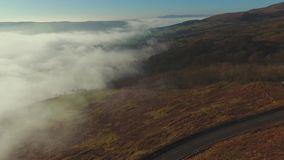 Mist in Valley. Aerial view above bright mist in a valley at the Campsie hills in Scotland. Hillside with bracken and clear blue sky above stock video