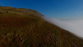 Mist in Valley. Aerial view above bright mist in a valley at the Campsie hills in Scotland. Hillside with bracken and clear blue sky above stock footage