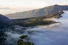 Mist vs Landscape. Dramatic Java landscape, near Mount Bromo - an active volcano. Mist sweeping around town and covering forest Royalty Free Stock Photo