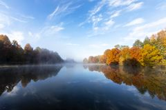 Mist on the water and autumn colored trees. South Africa royalty free stock photography