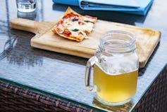 Misted стекло светлого пива и части полу-съеденной пиццы на таблице Стоковые Изображения