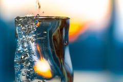 Misted exponeringsglas med den kalla alkoholdrinken eller vatten och vibrerande solnedgång Royaltyfri Fotografi