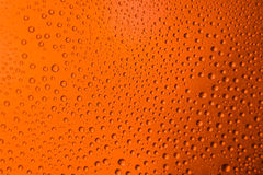 Misted glass of beer close up an orange bright background. Misted glass of beer close up of an orange bright background Stock Photo