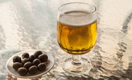 Misted glass of beer with olives on a glass table Stock Image