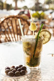 Misted glass of mojito with olives on a glass table Royalty Free Stock Images