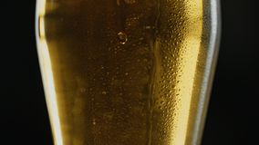 Misted mug of cold light kraft beer, drops flow down the glass, in bar or pub. Close up panorama shot. Isolated black background. Slow motion stock footage