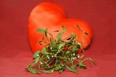 Mistelzweigblume auf rotem Hintergrundherzen Lizenzfreies Stockfoto