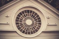 The mister behind the circular window. Sepia image of an old circular window - Hampton, New Hampshire stock photo