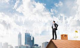 Mister boss on brick roof with arms akimbo. Mixed media Royalty Free Stock Image