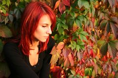 Misterious girl. Girl with red hair nier the colored leaves Stock Photo