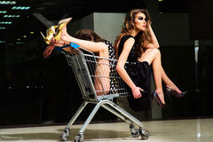 Misterious girls with shopping trolley Royalty Free Stock Photography