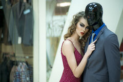 Misterious woman and mannequin. Misterious young woman with bright makeup and curly hair standing with male mannequin in formal clothes on shopping background Royalty Free Stock Photos