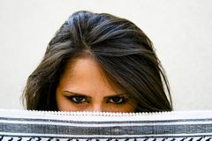 Mistery Woman. Young brunette woman showing only her brown eyes royalty free stock photo
