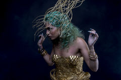 Mistic, Latin woman with green hair and gold tiara, wears a hand. Fitness Latin woman with green hair and gold costume with handmade flourishes, fantasy image Stock Photography