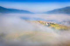 Mistige de zomerochtend in het bergdorp Stock Foto's