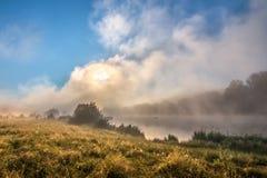 Mistige ochtend op de rivier - wolken skyes en gras Royalty-vrije Stock Foto